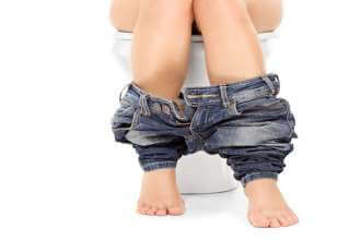 Female seated at a toilet with her pants down