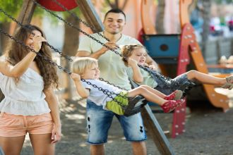 Small daughters on swings with young parents. Focus on woman